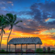 Sunrise over the Juno Beach Pier over coconut tree with bench under the tiki hut. HDR image from three exposure merged in Photomatix Pro and Topaz Software.