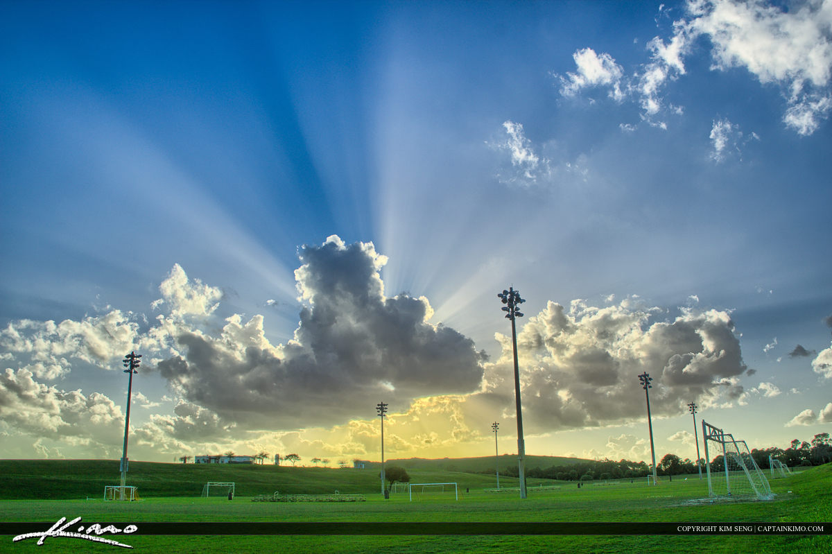 Outdoor Sports Soccer Field with Sunrays in Sky