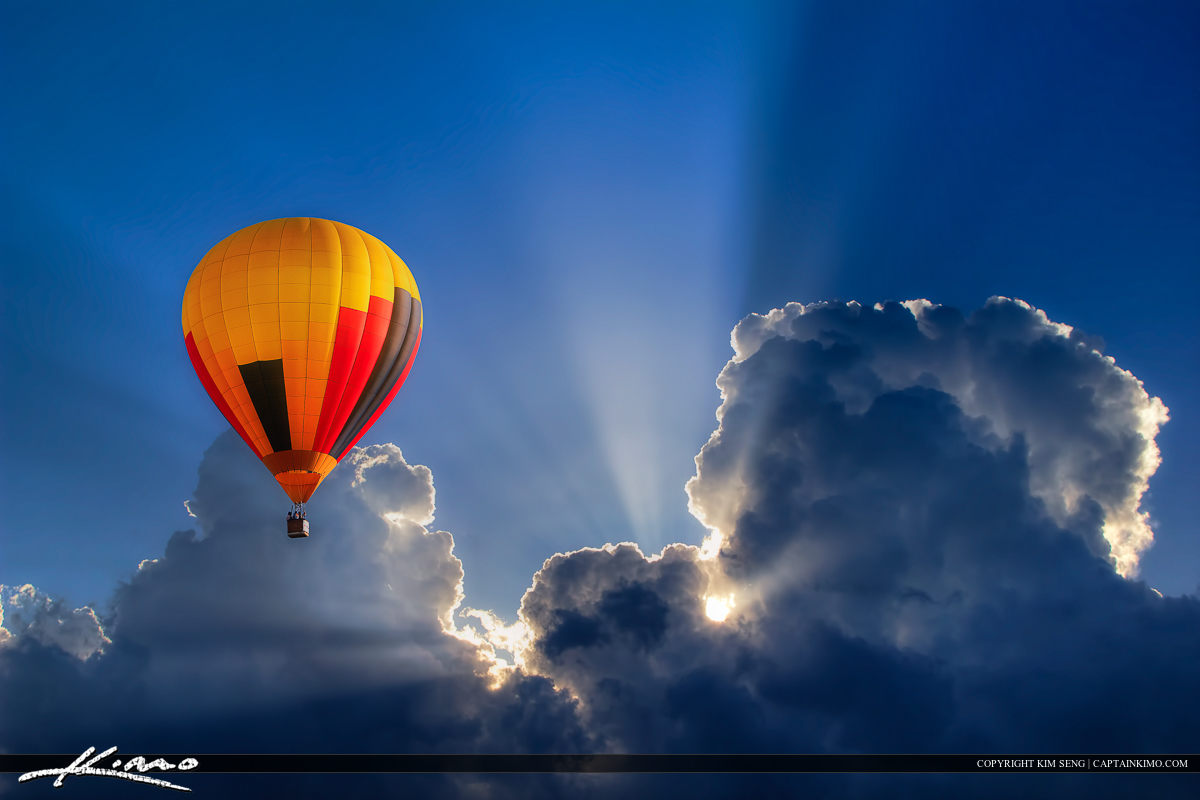 Hot Air Balloon High in Blue Cloudy Sky with Sunrays