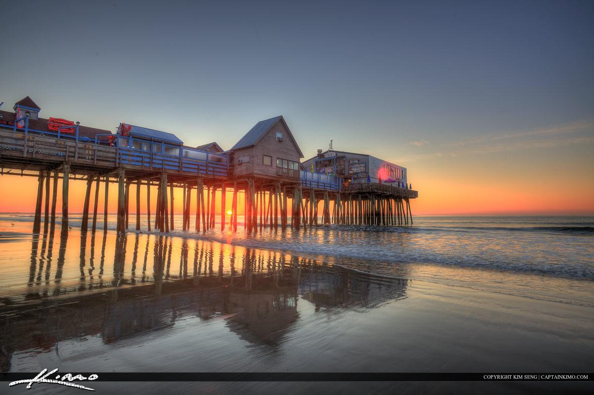 Sun rising between stilts at old Orchard Beach pier